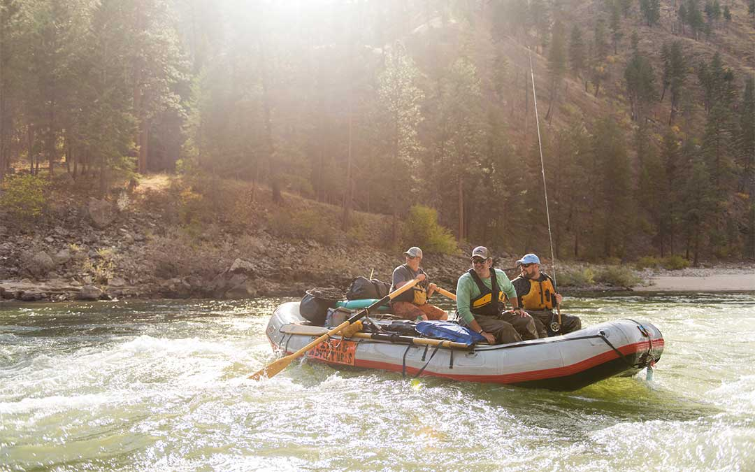 A group of anglers row through rough water in a raft